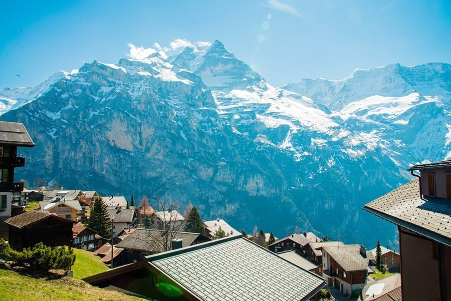 The Snow-covered Swiss Alps in background and Green field at Murren Village, Jungfrau region, Switzerland - April, 2016