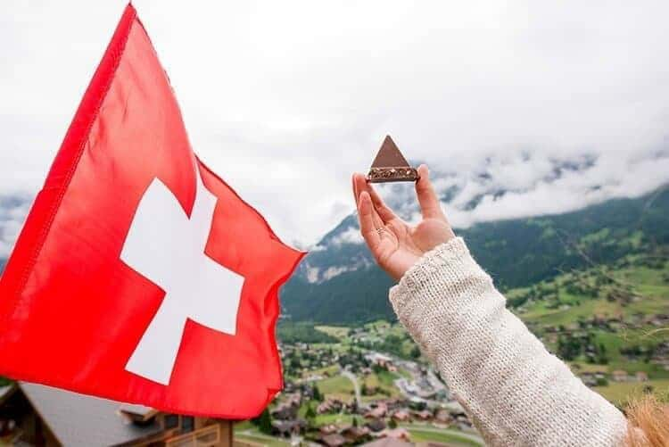 Holding traditional chocolate in form of triangle with swiss flag on the mountain background in Switzerland