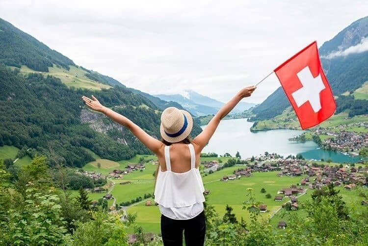 Young woman with swiss flag enjoying great landscape view on the valley with lake and village in Switzerland.