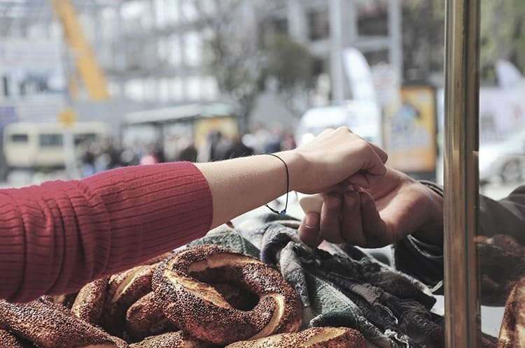 female hand giving money to get Turkish bagel at street