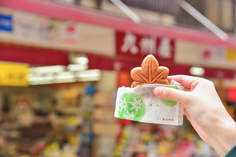 Hand Holding a Green Tea Momiji Manju, or Japanese-Style Sweet Cake Filled with Green Tea Paste