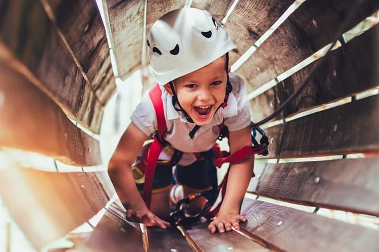 Little boy climbing in adventure activity park with helmet and safety equipment
