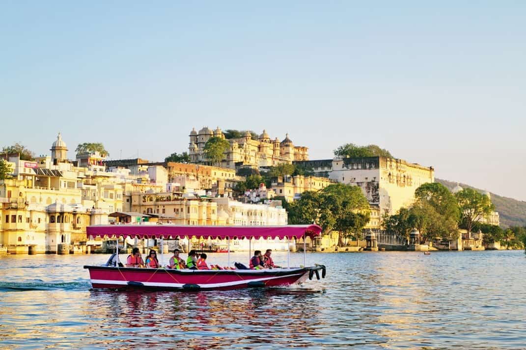 Tourists on the boat taking Udaipur Lake Pichola sunset boat ride with City Palace on background