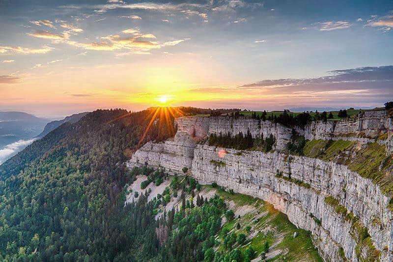 Vivid sunset with sunstar over cliff Creux du Van Neuchatel in warm light with sceenic view on valley and green forest